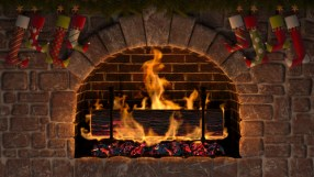 Burning Yule Log in fireplace decorated with christmas stockings.