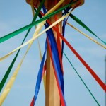 Maypole with colored ribbons unfurling, sunny skies