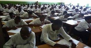 Photo des élèves dans une salle de classe en train de passer un examen.