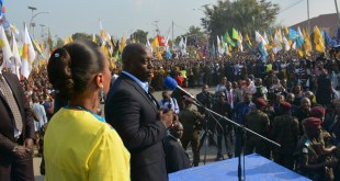 Photo d'un president congolais et sa femme a cote, en train de s'addresser a une foule.