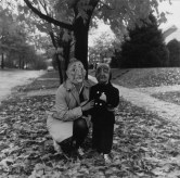 Black and white photograph of two masked figures on a leaf-covered front lawn front lawn