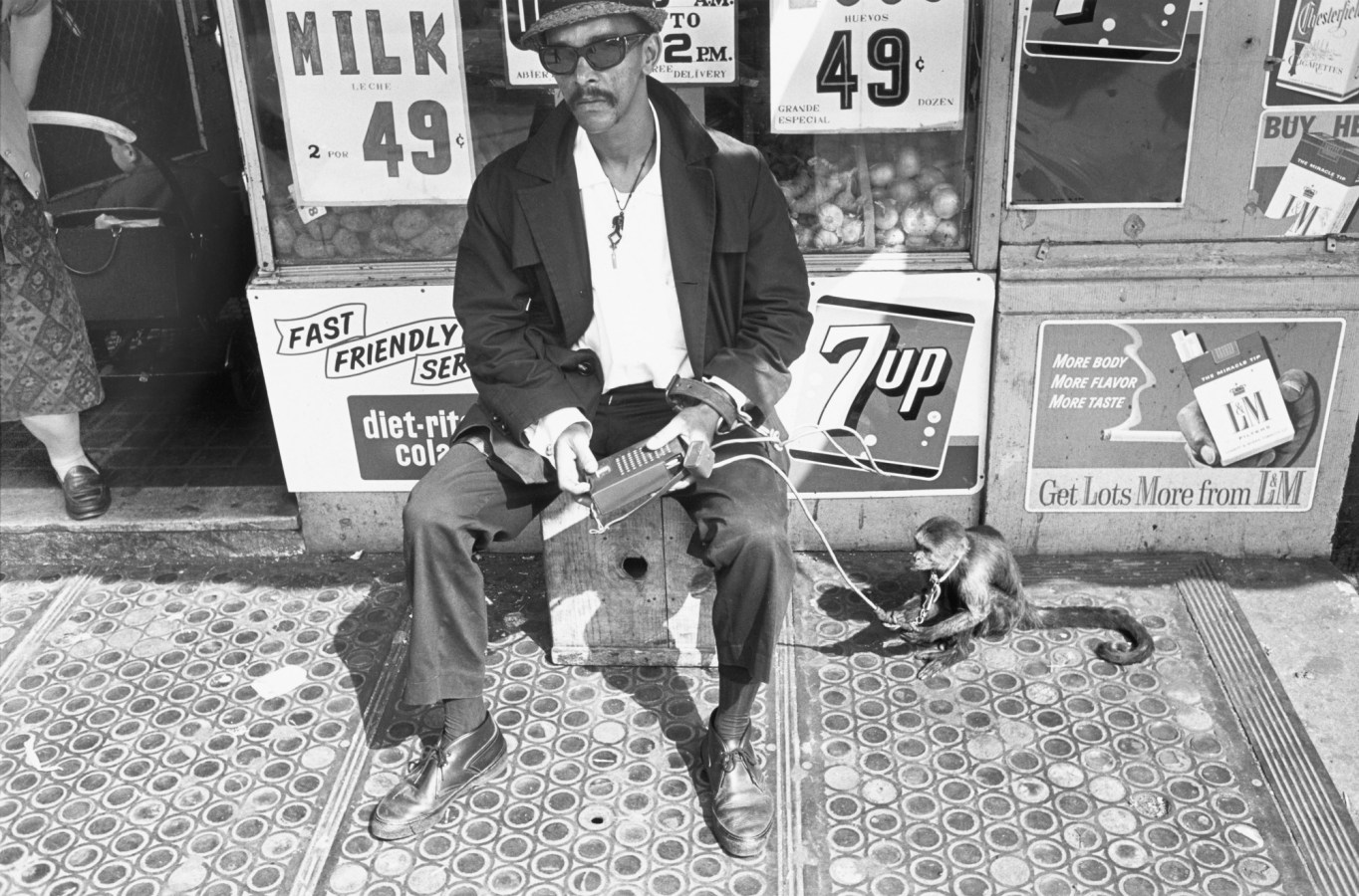 Black-and-white photograph of a man and a monkey sitting in front of a store with advertisements in the background
