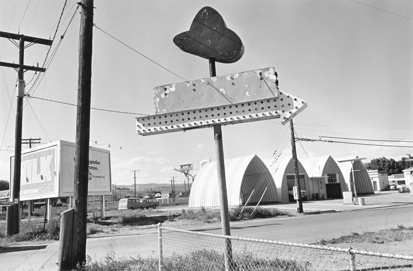 Black-and-white photograph of an old weathered neon sign shaped like a cowboy hat with an arrow pointing right
