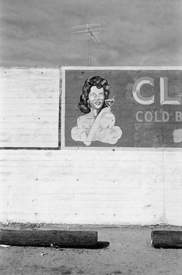 Black-and-white photograph of the side of a building with a hand painted sign of a woman holding a cocktail