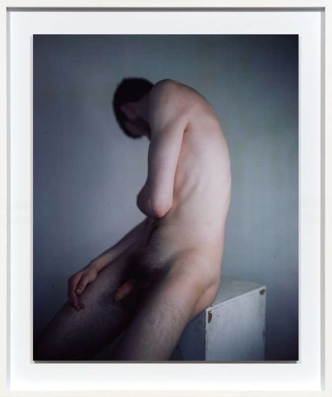 Color photographic portrait of a nude man seated on a plinth with his face turned to his shoulder away from the camera