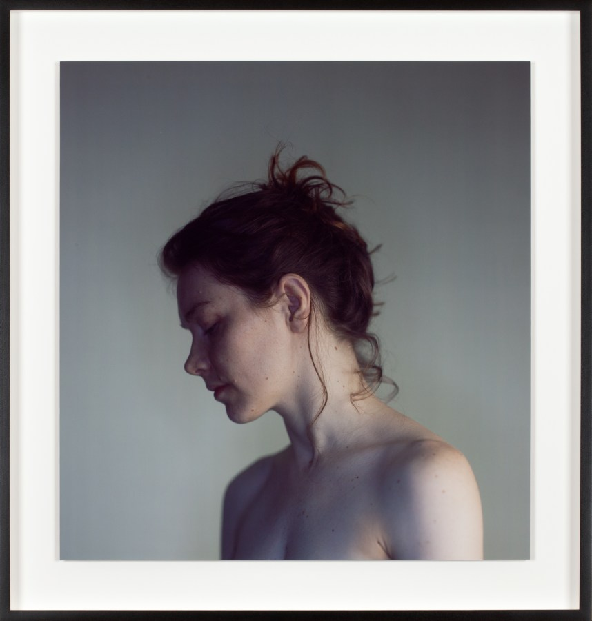 Color photographic portrait of the facial profile and shoulders of a topless young woman with her eyes closed and hair tied up