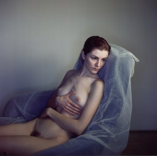 Color photographic portrait of a nude young woman reclining in a plastic-covered chair