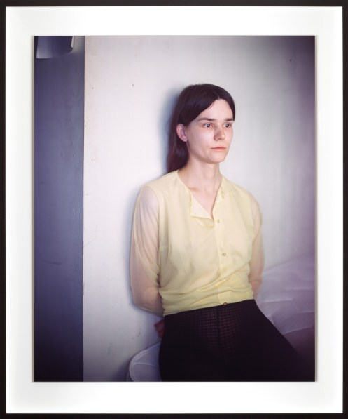 Color photographic portrait of a seated young woman in a yellow shirt leaning on a wall with her arms behind her back