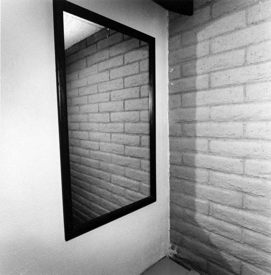 A black and white photograph of room corner with a brick wall reflected in a mirror