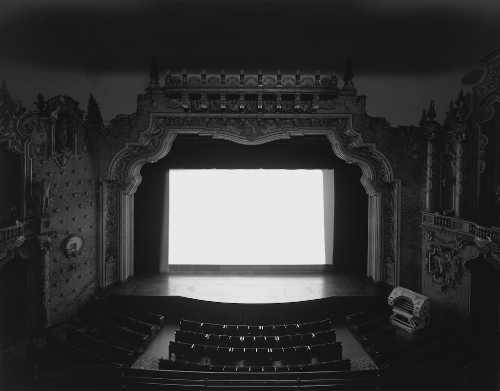 Black-and-white photograph of an empty theater with a glowing white screen onstage