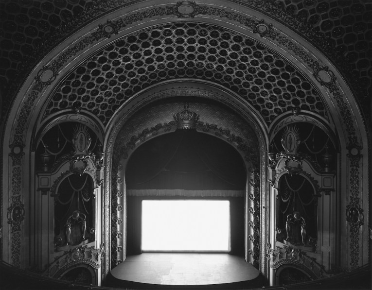 Black-and-white photograph of an empty theater with a coffered domed ceiling and glowing white screen onstage