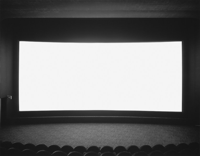 Black-and-white photograph of an empty theater with a wide glowing white screen