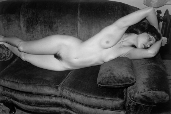 Black-and-white photograph of a nude woman posed on a couch