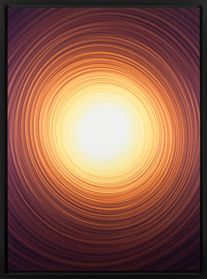 Color photograph of a bright yellow-white circle emanating fading orange rings of light on a black background