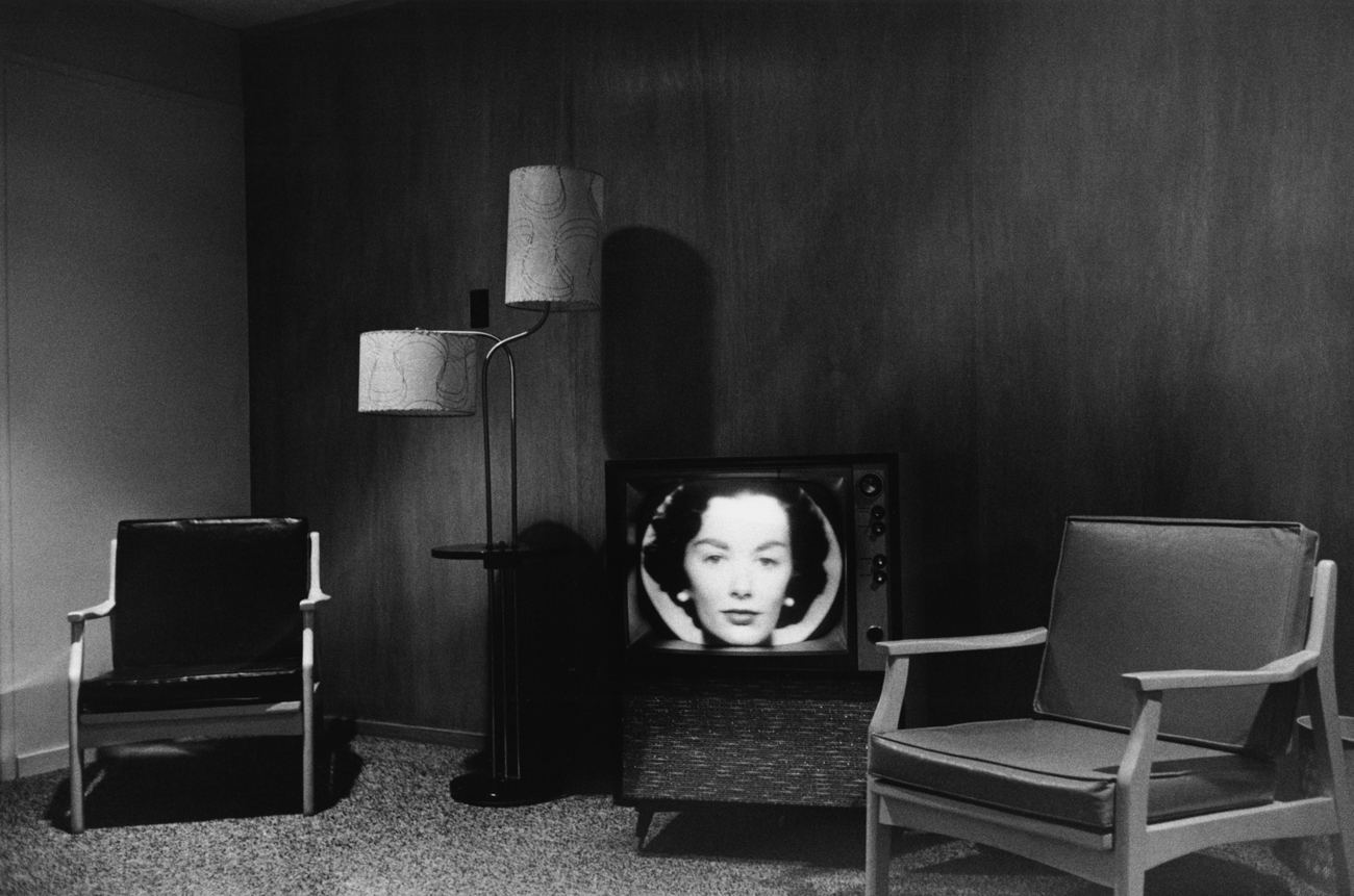Black-and-white photograph of an empty living room with a woman's face on the television