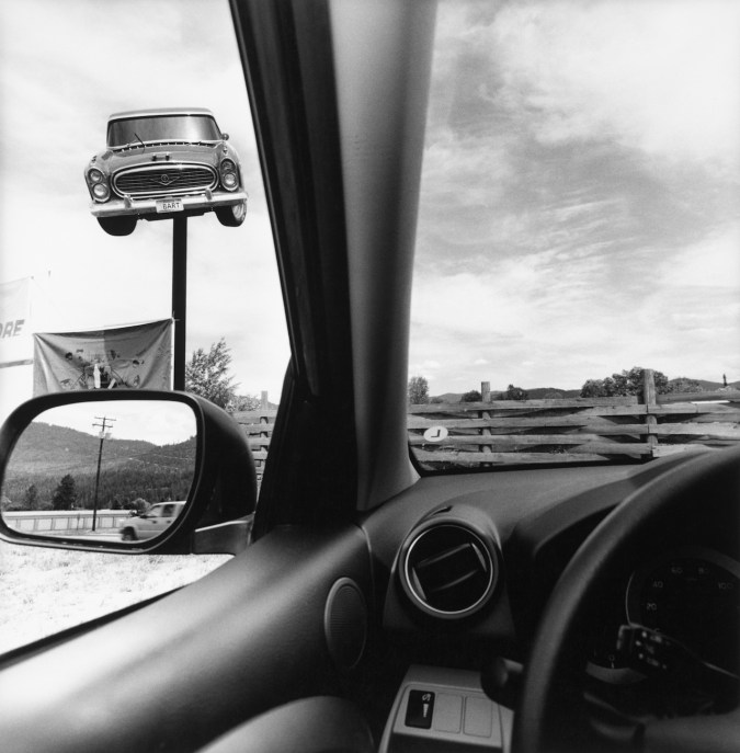 Black-and-white photograph from the drivers seat of a car showing the interior of the car and an advertisement of a 1950s car mounted on top of a pole
