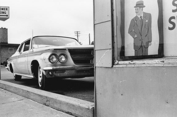 Black-and-white photograph of a parked car and an advertisement showing a man in a suit and hat