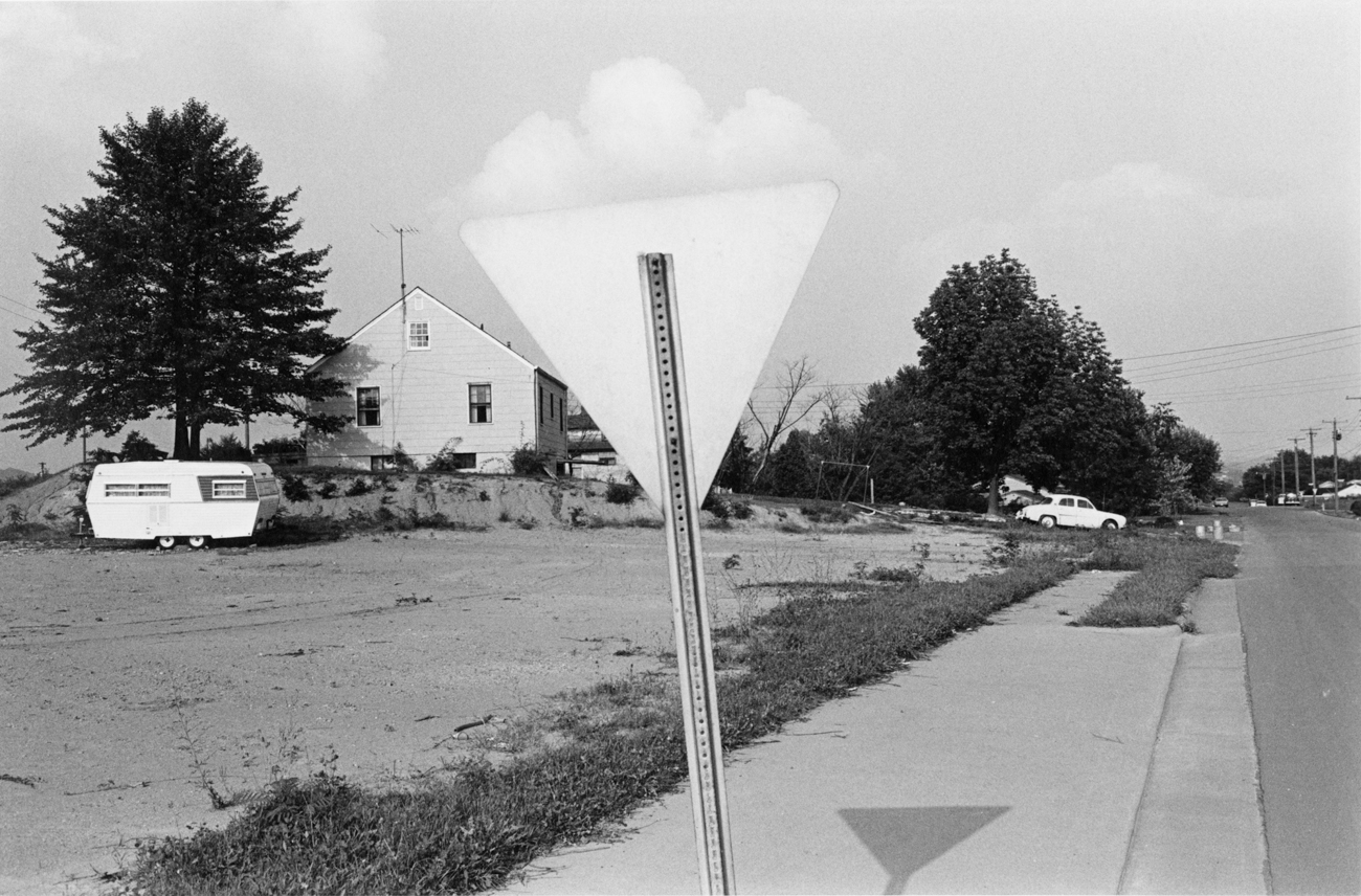 Black-and-white photograph of the back of a yield sign with a cloud positioned directly above the sign