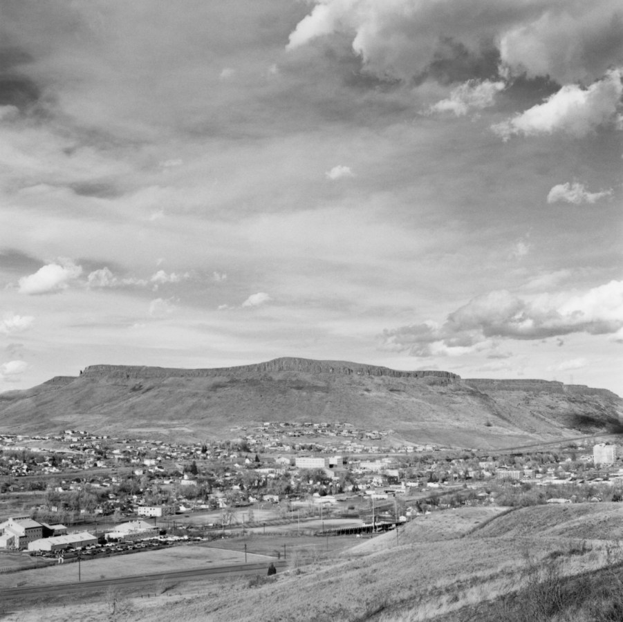 A black and white photograph overlooking a small town with mountains and clouds in the distance.