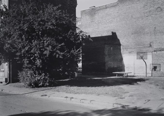 Black-and-white horizontal photograph of an empty street with a tree, ping-pong table, and basketball court.
