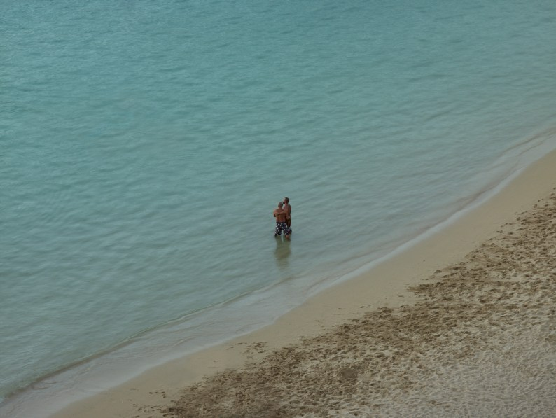 Color photograph of two men standing in knee-deep water near the shore of a calm sea