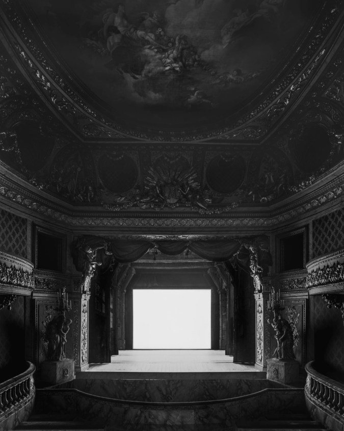 Black-and-white photograph of an empty Baroque European theater with a glowing white blank screen on stage