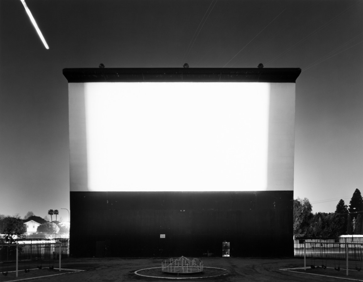 Black-and-white photograph of a blank white outdoor movie screen against an American suburb