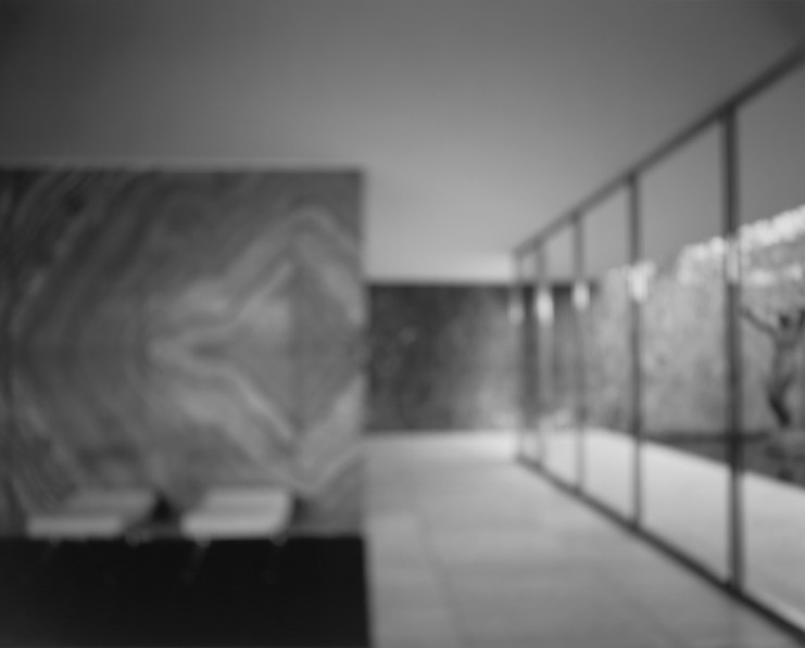 Black-and-white photograph of out of focus interior of a minimalist building with an arcade of windows on the right and seating area on the left