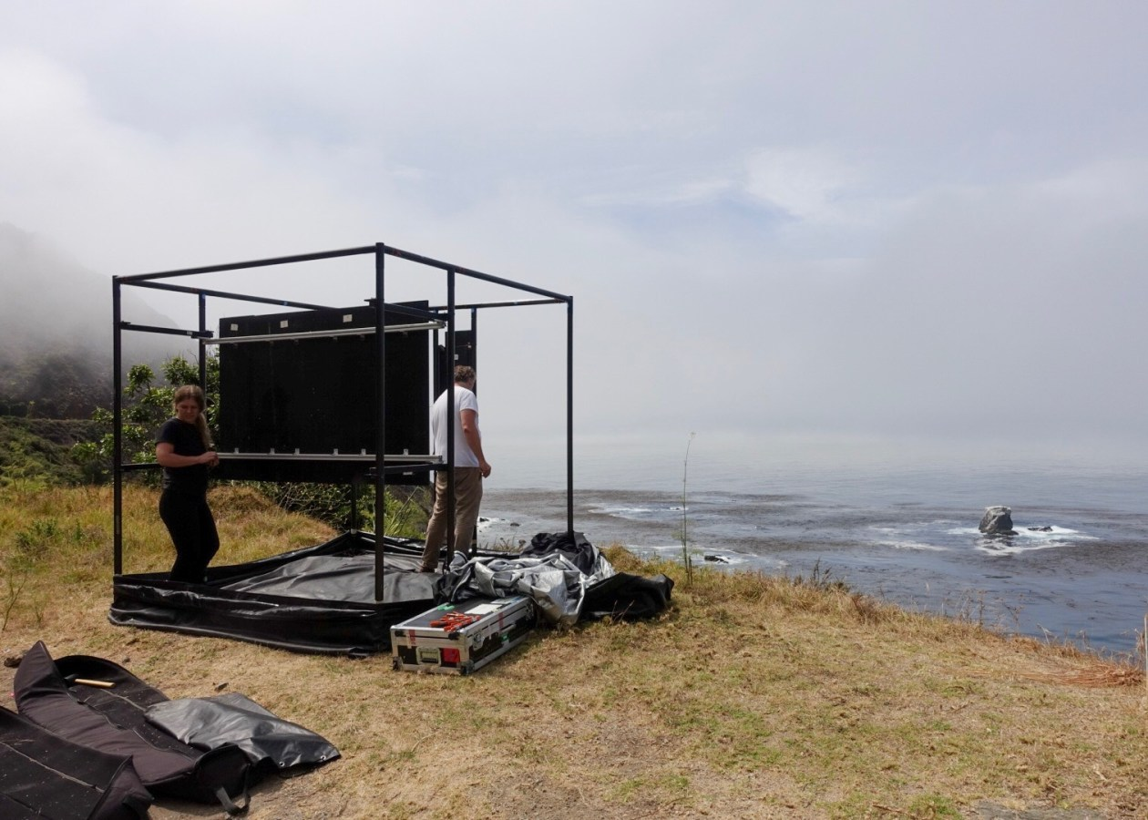 Color photograph of a large cube-shaped armature on the shoreline, with two persons inside.
