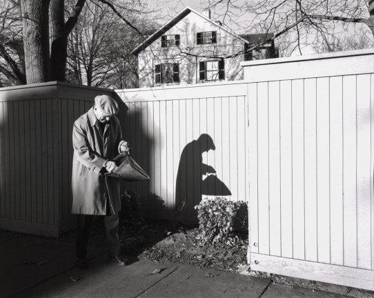 Black-and-white photograph of an older man pausing on a street next to a white fence to look in his bag
