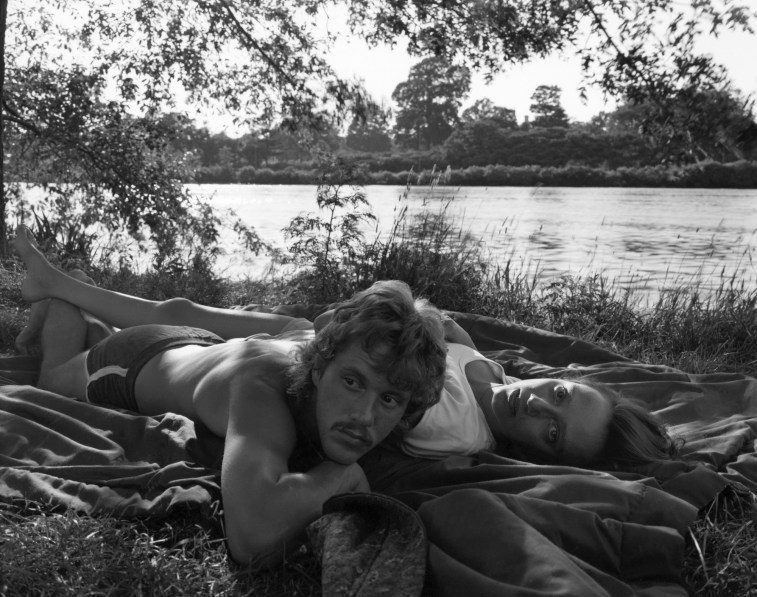 Black-and-white photograph of a man and a woman lying on a blanket next to a riverbank