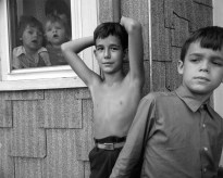 Black-and-white photograph of two young boys against a shingled wall next to a window with two toddlers looking out