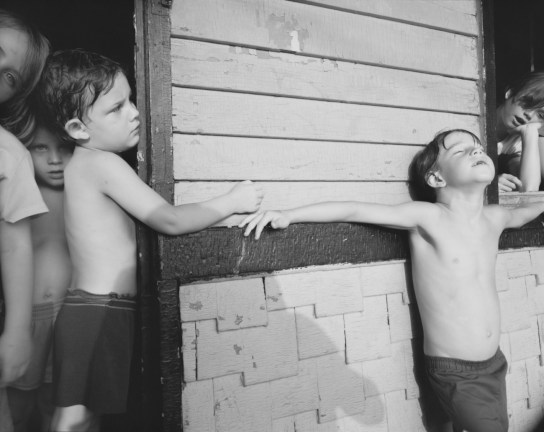 Black-and-white photograph of young children peering out of an open doorway and window with a boy leaning on the outer wall