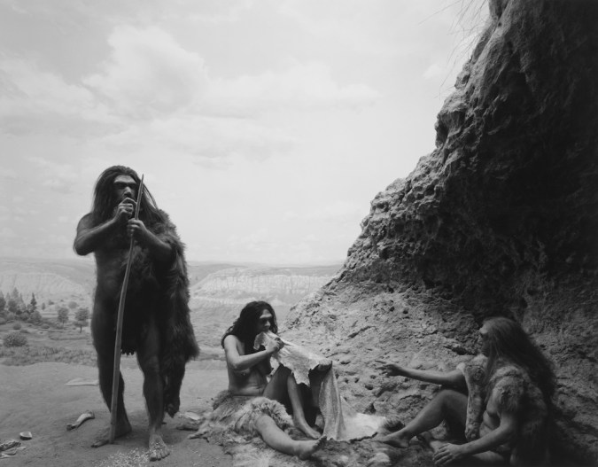 Black-and-white photograph of a museum diorama of early humans working with animal skins