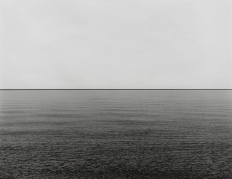 Black-and-white photograph of a calm waterscape across the lower half with a blank light gray sky above