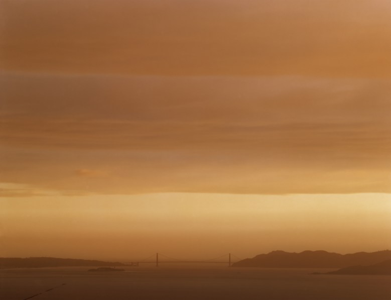 Color photograph of the distant Golden Gate Bridge under an overcast orange sky at sunset