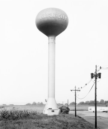 Black-and-white photograph of a water tower against a clear sky