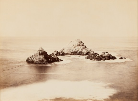 Albumen photograph of a grouping of pointed rocks jutting out of a flat expanse of ocean