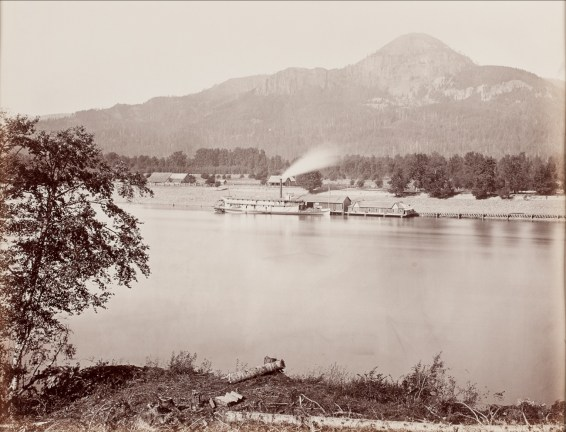 Albumen photograph of a steamship docked by boathouses on a wide river in front of a mountain