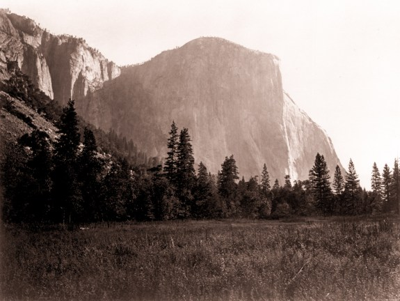 Albumen photograph of a meadow with pine trees at the base of a towering rounded rock outcrop