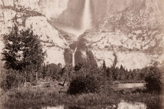Albumen photograph of a waterfall flowing down a vertical rock outcrop reflected in a river in the foreground
