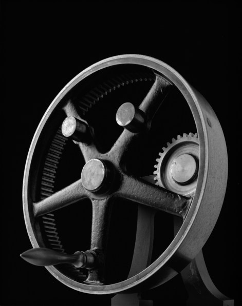 Black-and-white photograph of a round mechanism containing a single gear