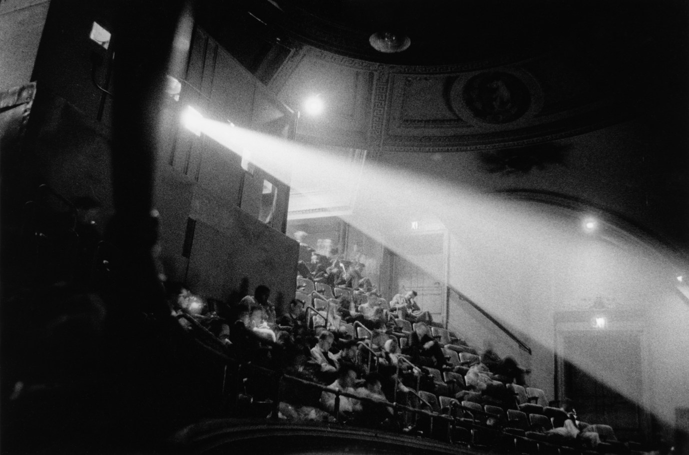 Black-and-white photograph of light from a movie projector streaming across a balcony