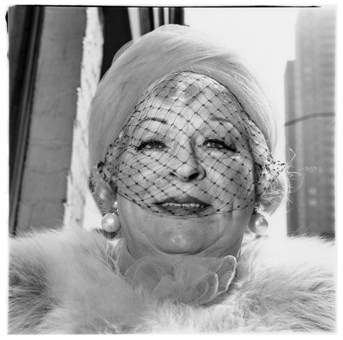 Black-and-white photograph of a woman wearing pearl earrings, a veil, and a fur collar