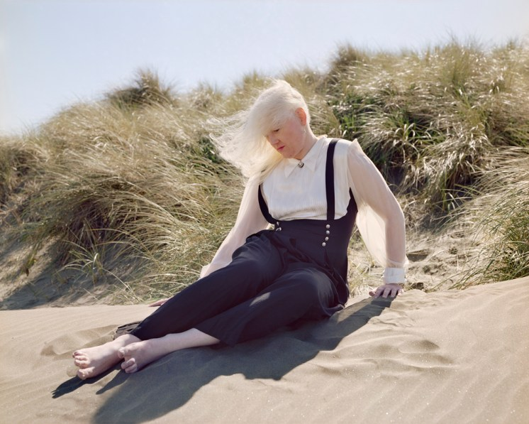 Color photograph of a woman with long white hair blowing in the wind seated on a sand dune covered with beach grasses