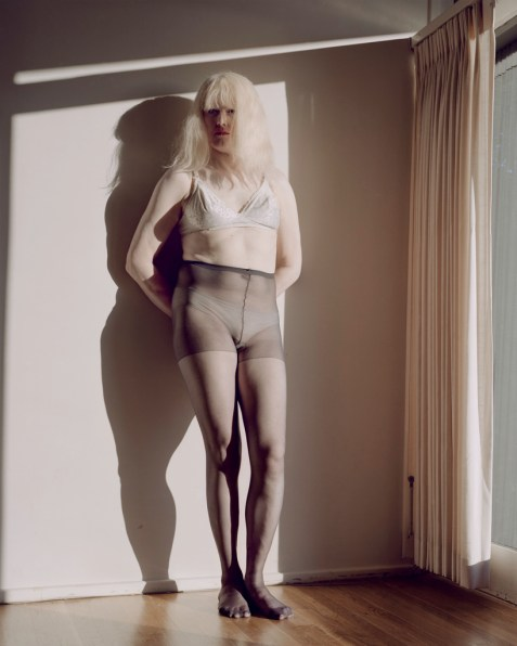 Color photograph of a woman with long white hair leaning against a wall next to a curtained window