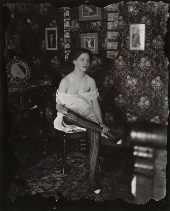 Black-and-white photograph of a woman with her legs crossed sitting in a wallpapered room