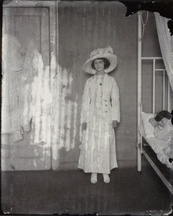 Black-and-white photograph of a woman wearing a dress and hat standing next to a bed