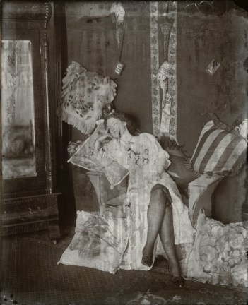 Black-and-white photograph of a woman sitting with her legs crossed surrounded by pillows