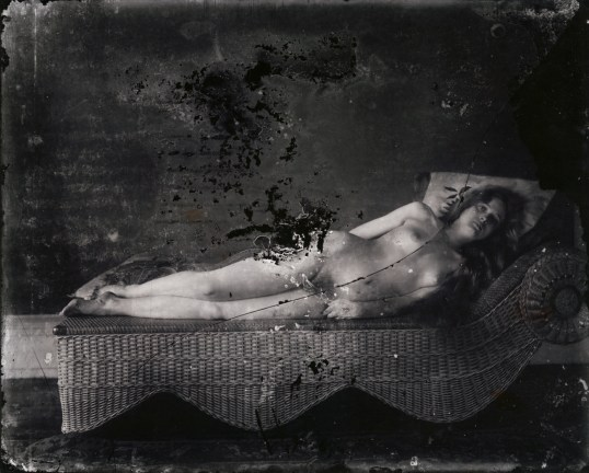 Black-and-white photograph of a nude woman laying on a wicker lounge chair